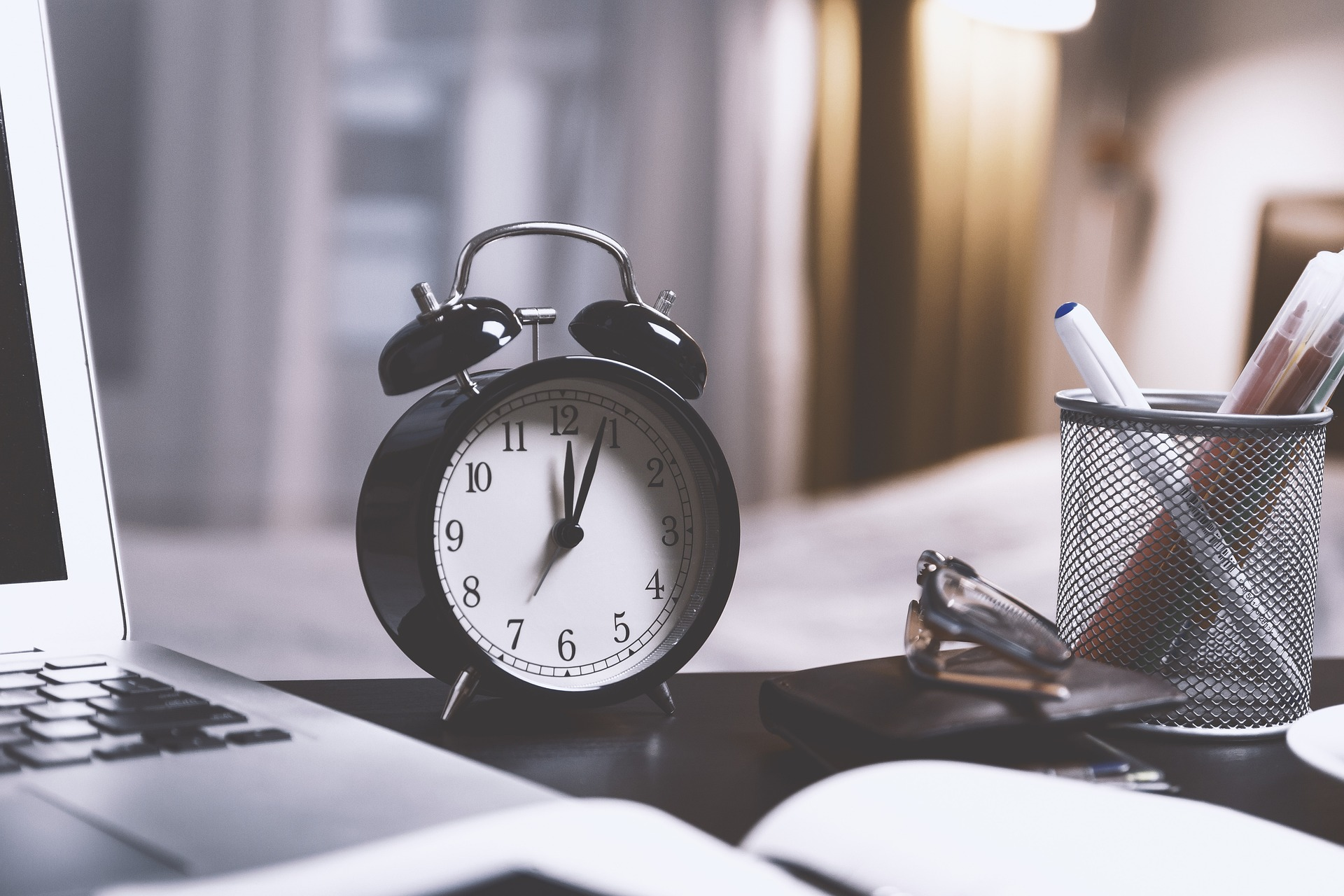 Uhr auf einem Schreibtisch mit Laptop und Notizbuch